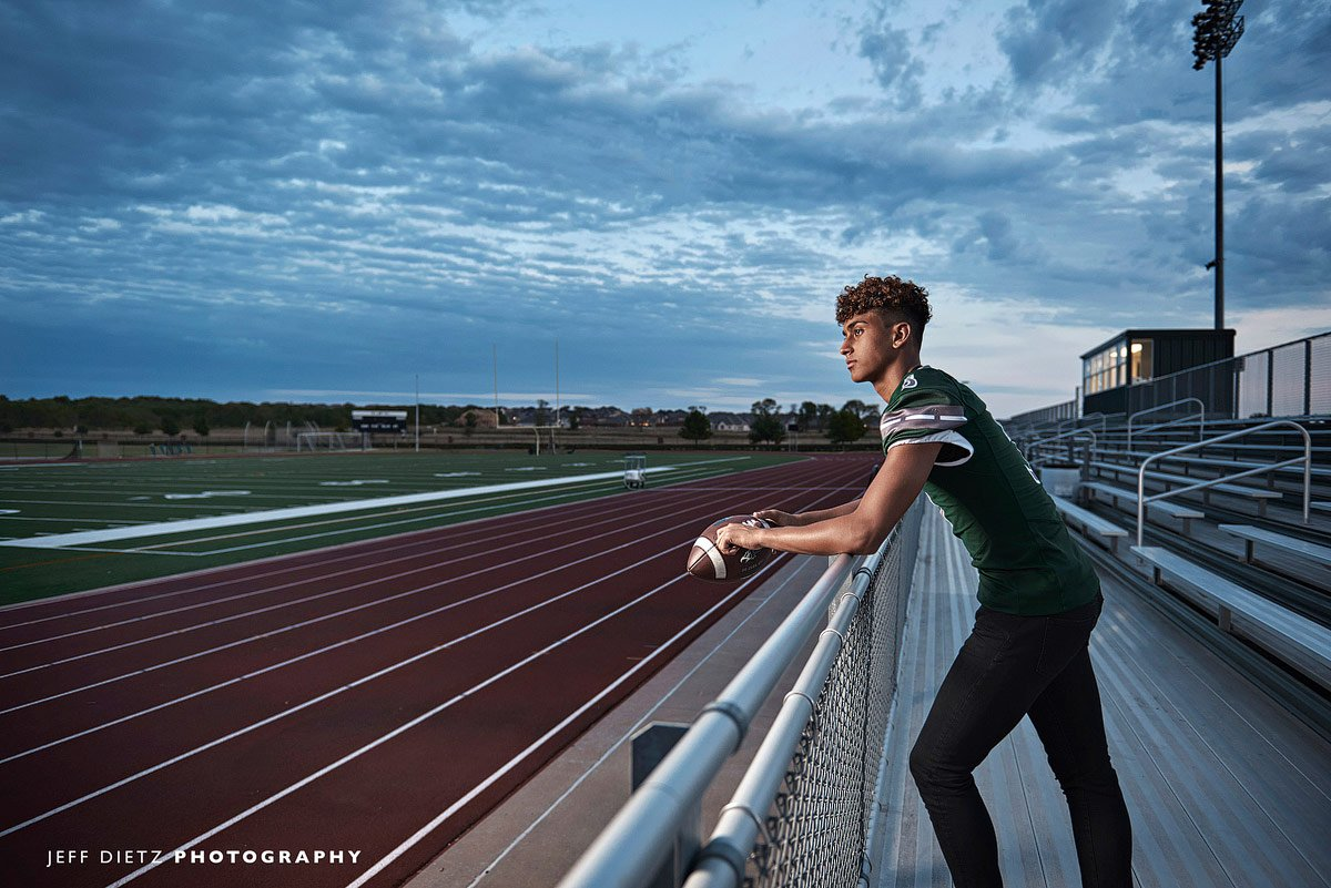 prosper football player stands in the bleachers overlooking the field for senior portraits
