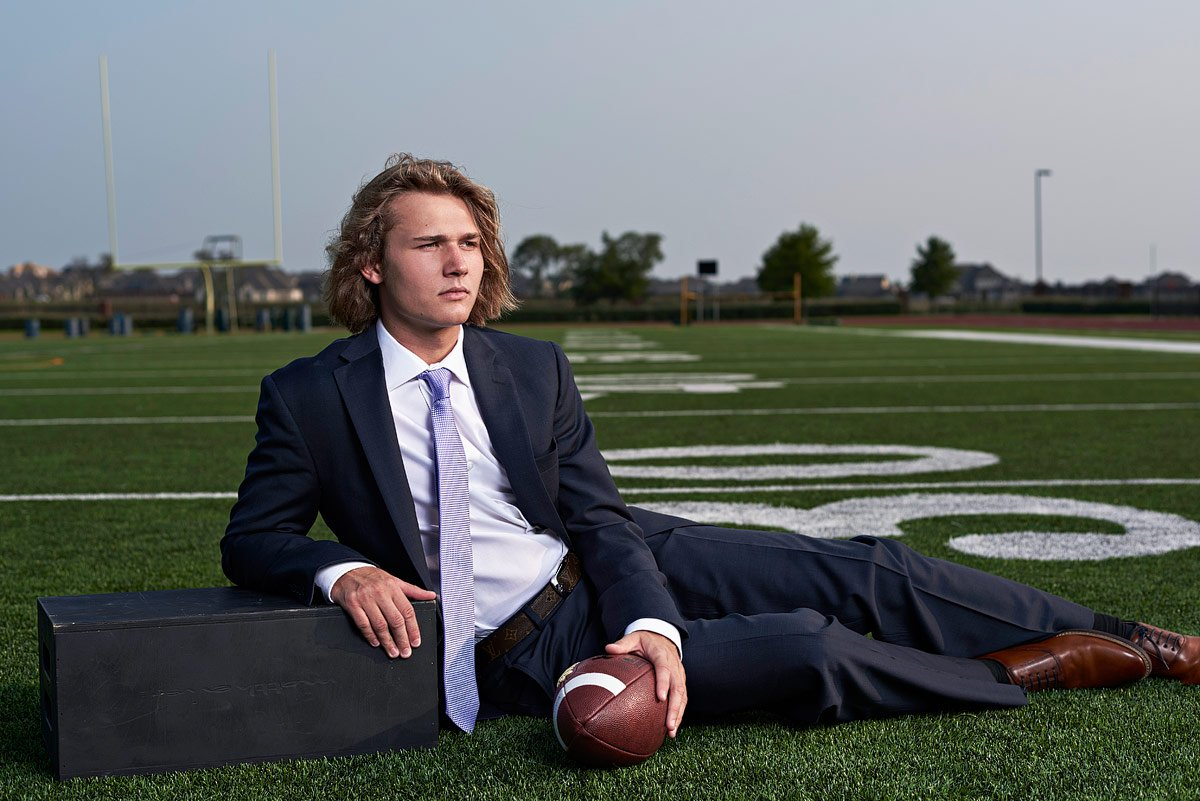 dallas senior portrait photographer from mckinney texas takes photos of prosper football player in a suit