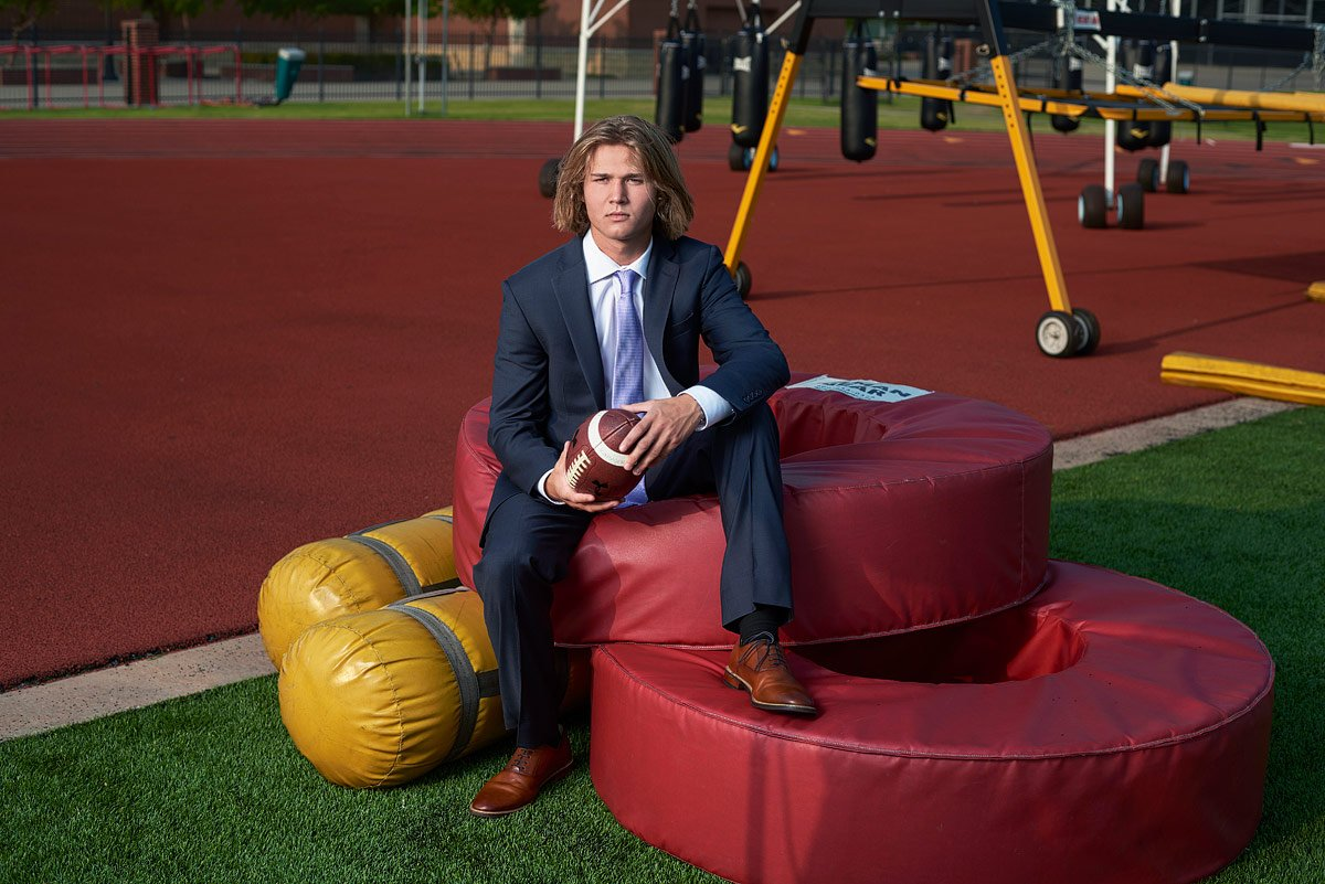 prosper senior at high school practice field for his senior photos posing by practice equipment