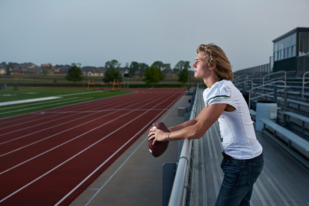 prosper high school senior looking over the field in his jersey for senior pictures