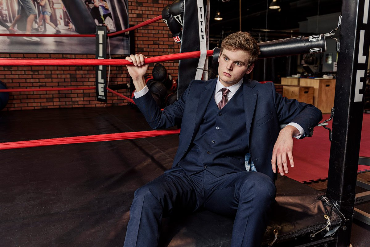 plano senior pictures at boxing gym sitting on the red ropes
