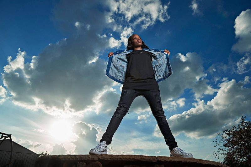 prosper girls basketball player stand on rock for senior portraits with jean jacket open