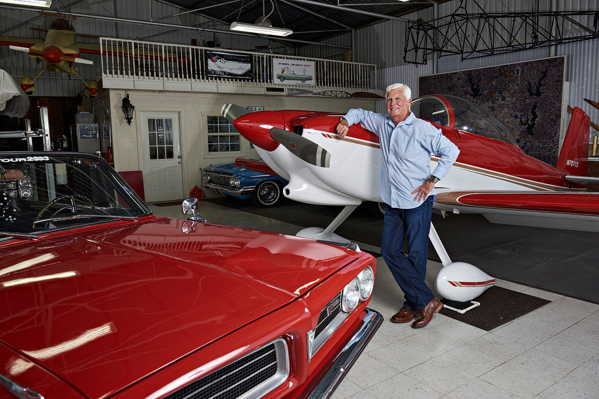 portrait next to private plane and car in aero country hanger mckinney texas