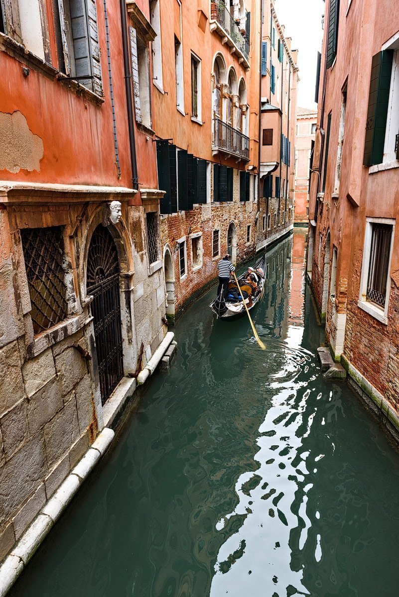 gondola goes down canal with orange houses venice photographer