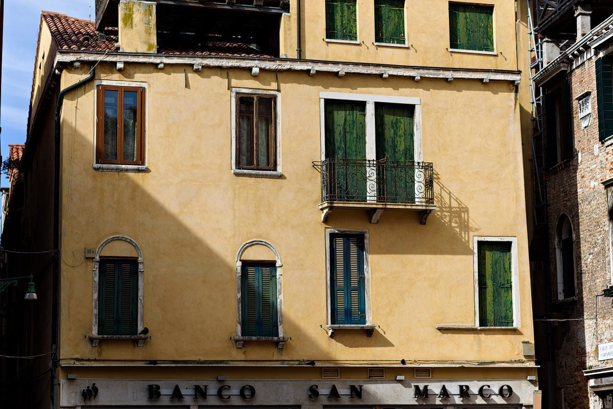 yellow building with green shutters in venice italy dallas travel photographer