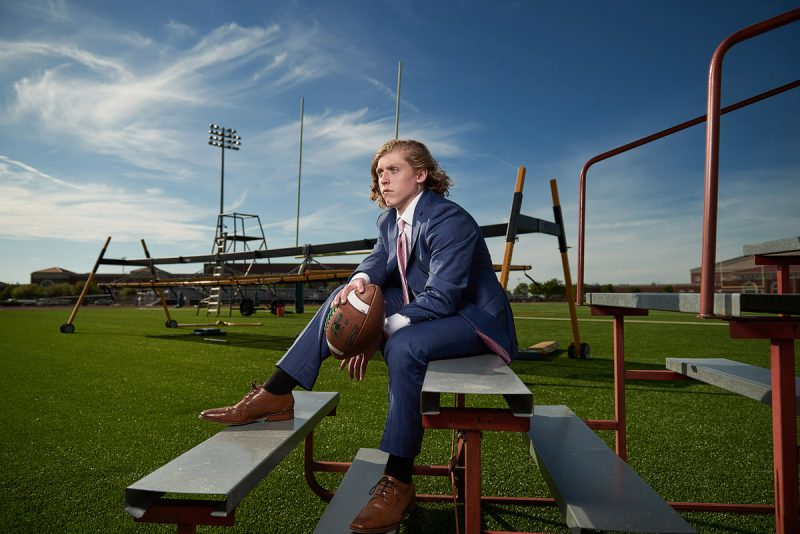 Prosper senior pictures of football player in suit at the practice field