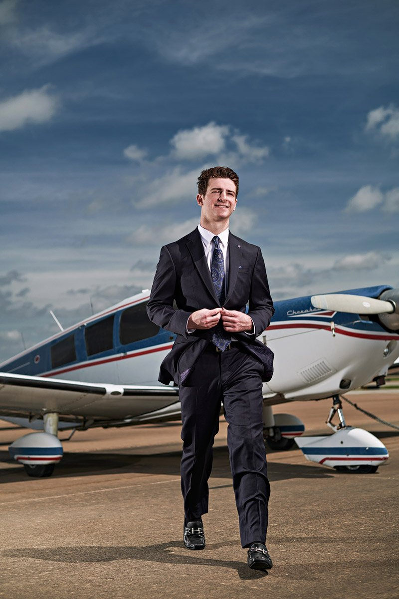 prosper senior photographer student walking away from airplane in suit