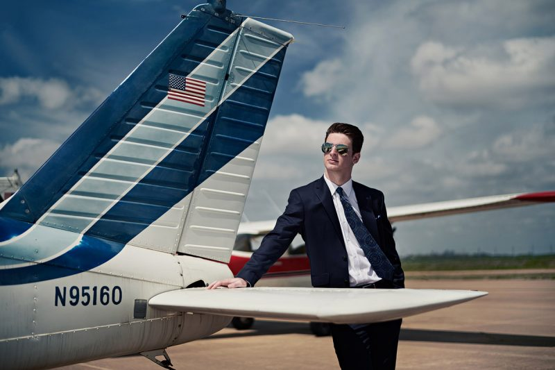 prosper senior photographer photographs student by plane with sunglasses