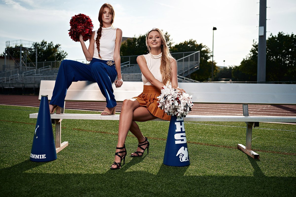 2 dallas cheerleaders friends pose for senior portraits on a bench at Allen ISD