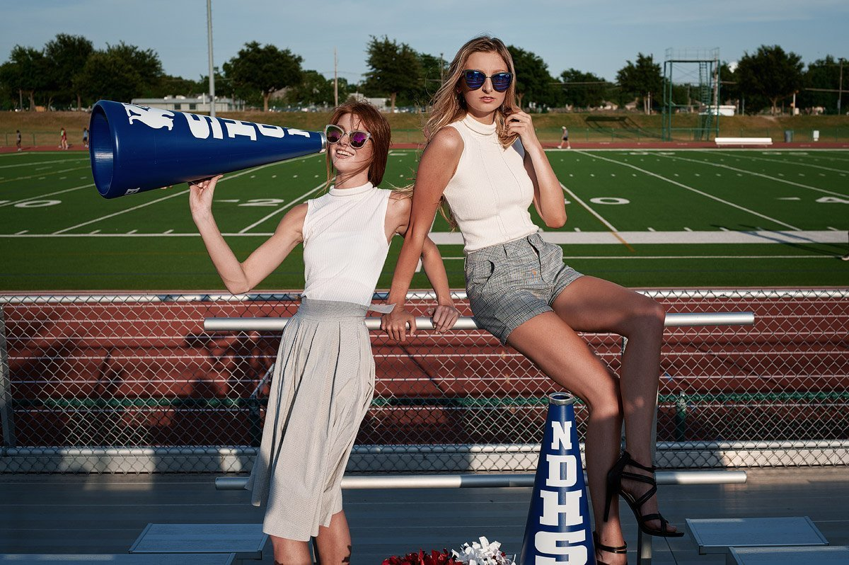 dallas cheerleader senior pictures with friends with a megaphone at allen stadium