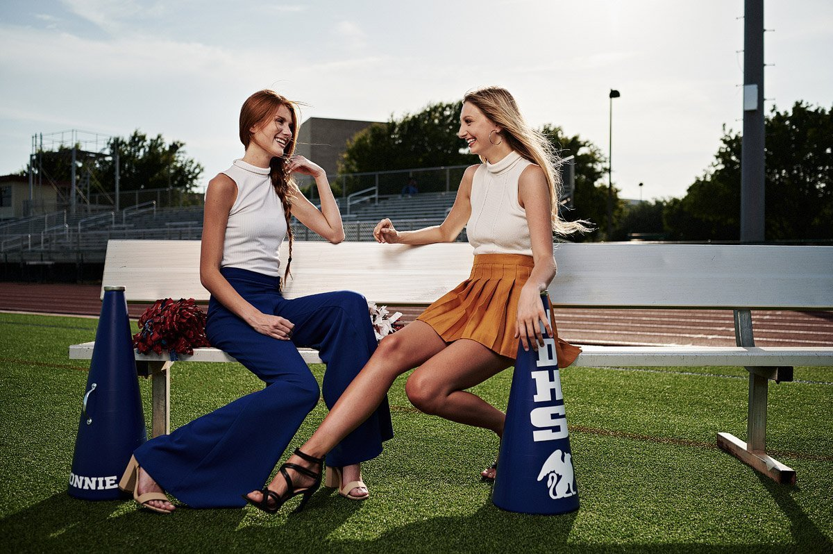 two allen cheerleaders posing for senior portraits on the football field